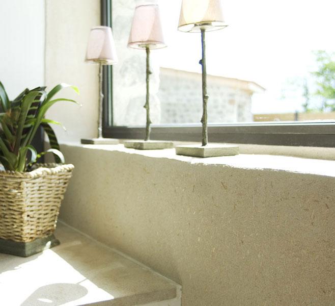 Application de l'enduit argile autour d'une fenêtre